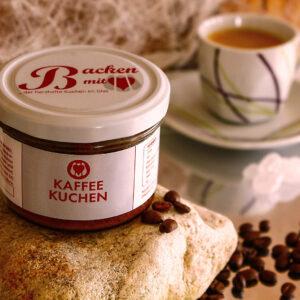 Kaffeekuchen steht auf einem Stein, im Hintergrund eine Tasse Kaffee, dekoriert mit Kaffeebohnen
