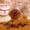 Ein Kaffeekuchen steht auf einem Stein, Zweiter Kuchen geöffnet daneben, ganz Rechts eine Kaffeetasse, im Vordergrund Kaffeebohnen