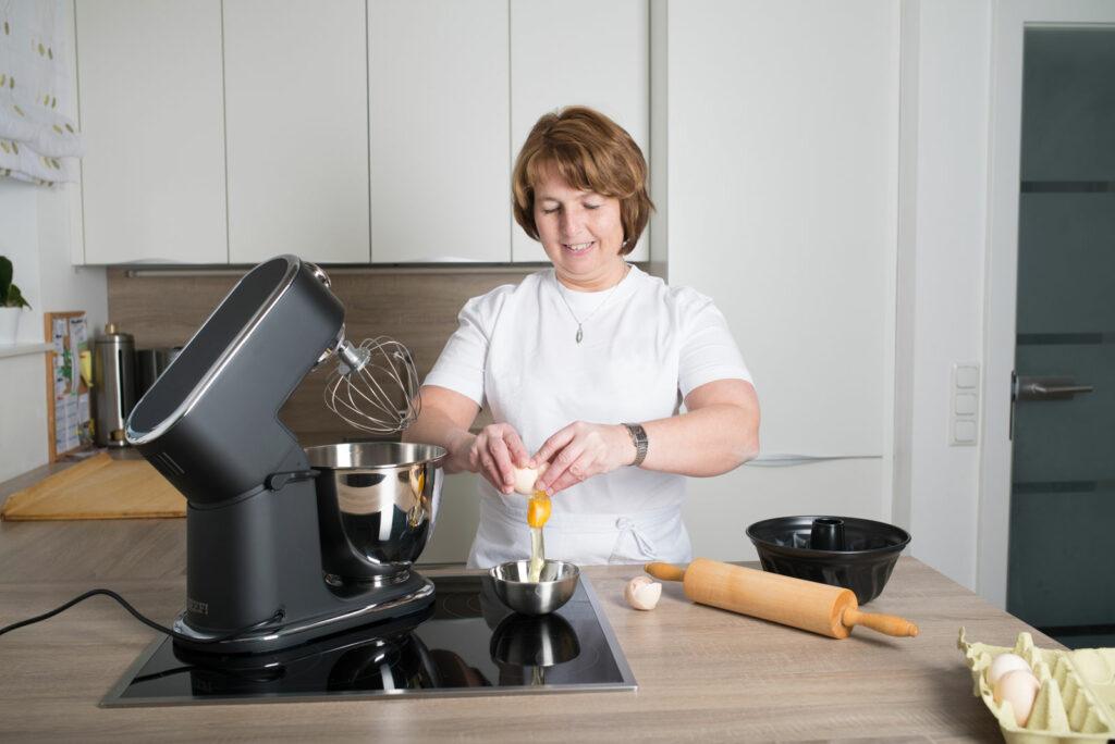 Maria schlägt gerade ein Ei auf, Links ein Nudelholz und eine Backform, Rechts ein Mixer