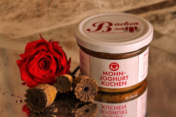 Mohn-Joghurt Kuchen auf einer Glasplatte, dekoriert mit Mohnblumen und einer roten Rose