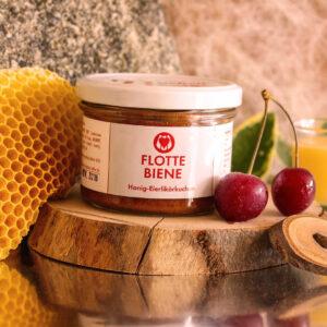 Flotte Biene Kuchen steht auf einem Holzbrett, dekoriert mit Honigwaben und Kirschen